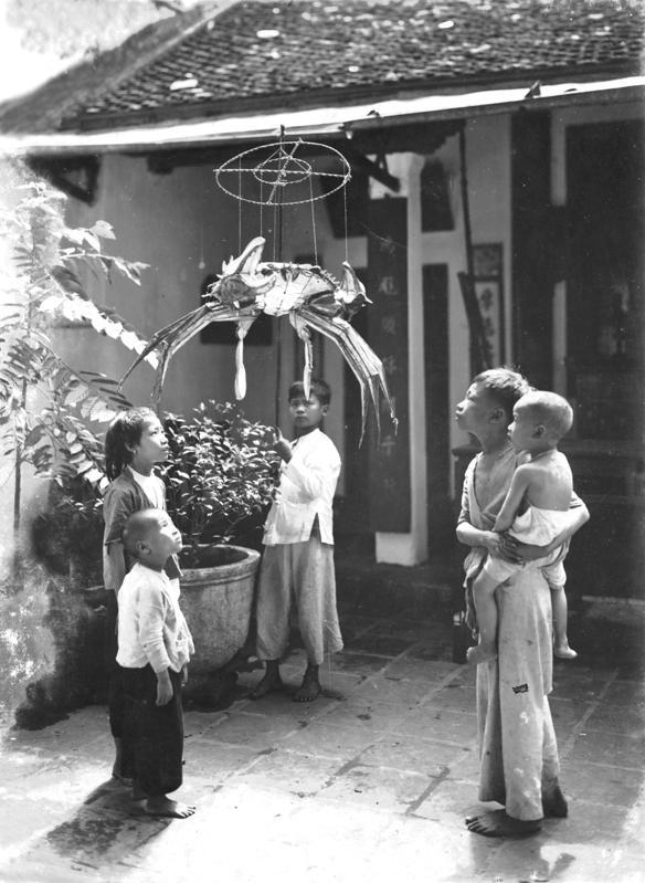 Những đứa trẻ ngắm nghía chiếc đèn lồng hình con cua được người lớn mua cho.